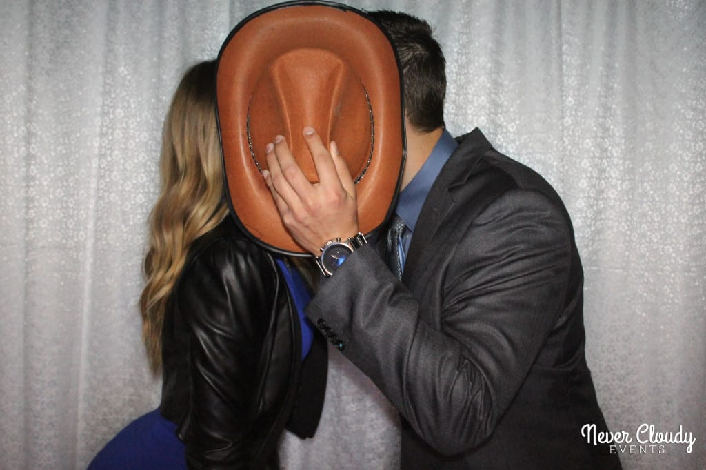 Couple kissing behind a hat in photo booth